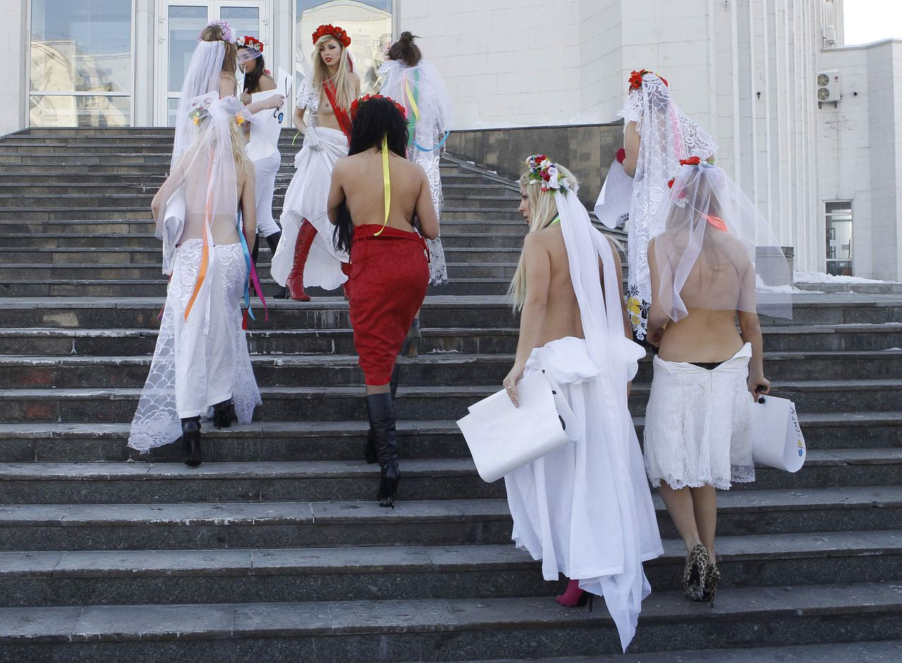 """Activists from the women's rights organization """"Femen"""", dressed as brides, arrive to take part in a rally in front of a wedding palace in Kiev March 1, 2011. """"Femen"""" was protesting against plans by a New Zealand radio station """"The Rock FM"""" to bring the winner of one of its competitions to Ukraine to find a woman to marry. REUTERS/Gleb Garanich (UKRAINE - Tags: CIVIL UNREST) TEMPLATE OUT"""