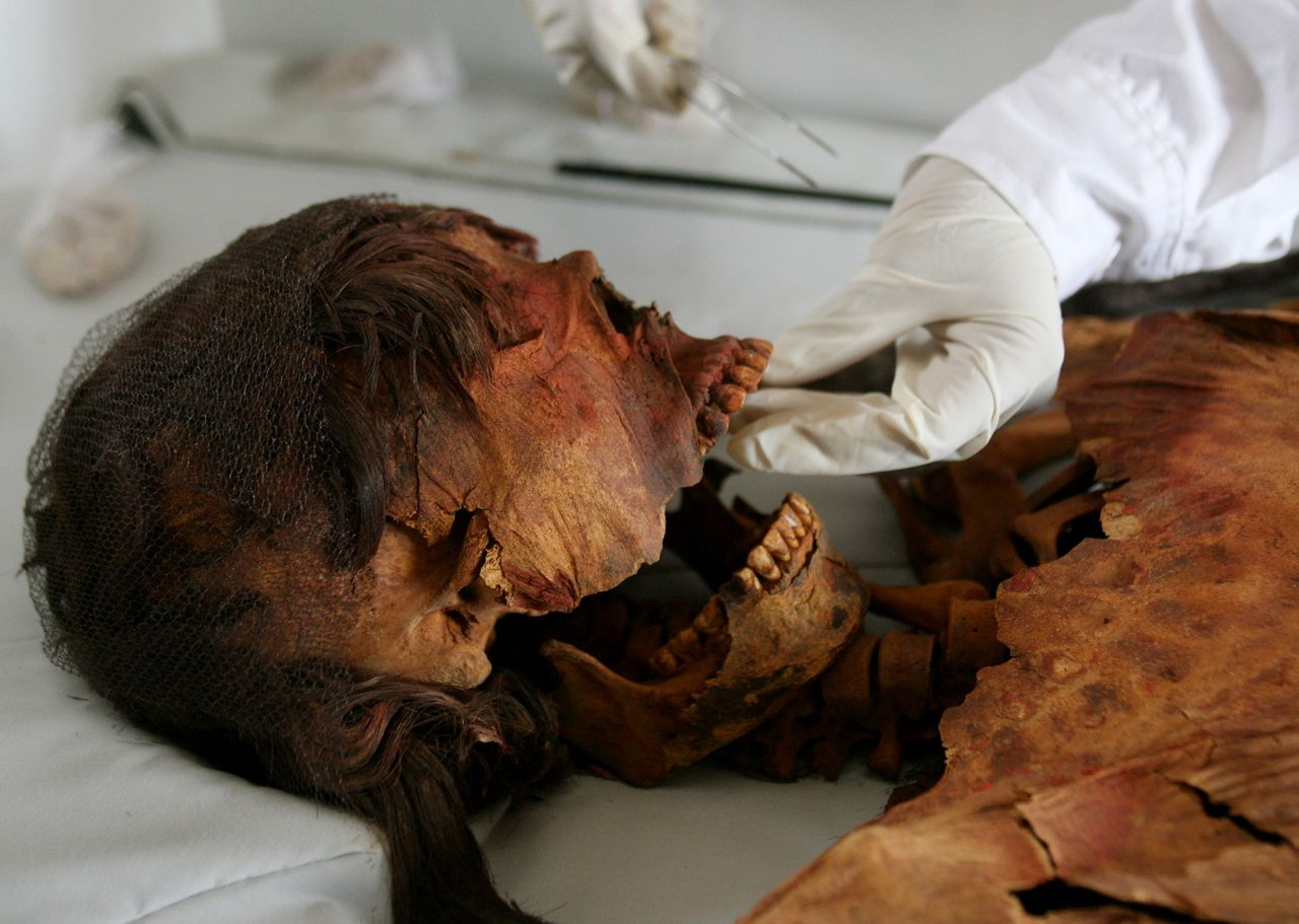 Mummie uit Andescultuur, ontdekt in Peru. (Foto Reuters) A Peruvian archaeologist inspects a mummy from the ancient Moche culture, part of it covered with tattoos, that was discovered at the pyramid Huaca Cao Viejo, located at a ceremonial site called El Brujo (the Wizard) in Trujillo, May 12, 2006. The elaborately wrapped mummy,a young woman who died in her late 20s and believed to have been a member of the Moche elite, is dated to around A.D. 450, according to Peruvian archaeologists. The site of Huaca Cao Viejo was opened for visitors after the Wiese Foundation/INC restored and covered the site. PICTURE TAKEN MAY 12, 2006. REUTERS/Mariana Bazo