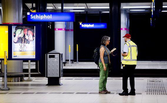 Een reizigster vraagt informatie op station Schiphol.