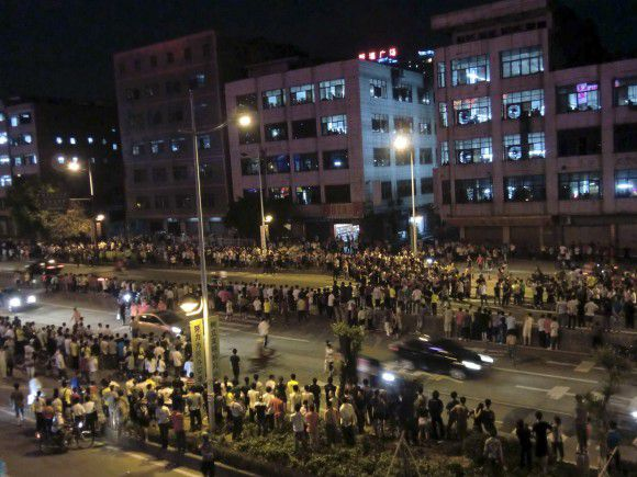 Hundreds of protesters stand off with riot police at a township in Zengcheng near the southern Chinese city of Guangzhou in the evening of June 12, 2011. Riot police fired tear gas over the weekend to disperse rampaging migrant workers in southern China who were protesting over the mistreatment of a young pregnant street hawker by security guards, media reports said on Monday. Picture taken June 12, 2011. REUTERS/Apple Daily (CHINA - Tags: POLITICS CIVIL UNREST EMPLOYMENT BUSINESS) NO SALES. NO ARCHIVES. FOR EDITORIAL USE ONLY. NOT FOR SALE FOR MARKETING OR ADVERTISING CAMPAIGNS. THIS IMAGE HAS BEEN SUPPLIED BY A THIRD PARTY. IT IS DISTRIBUTED, EXACTLY AS RECEIVED BY REUTERS, AS A SERVICE TO CLIENTS. HONG KONG OUT. NO COMMERCIAL OR EDITORIAL SALES IN HONG KONG. TAIWAN OUT. NO COMMERCIAL OR EDITORIAL SALES IN TAIWAN