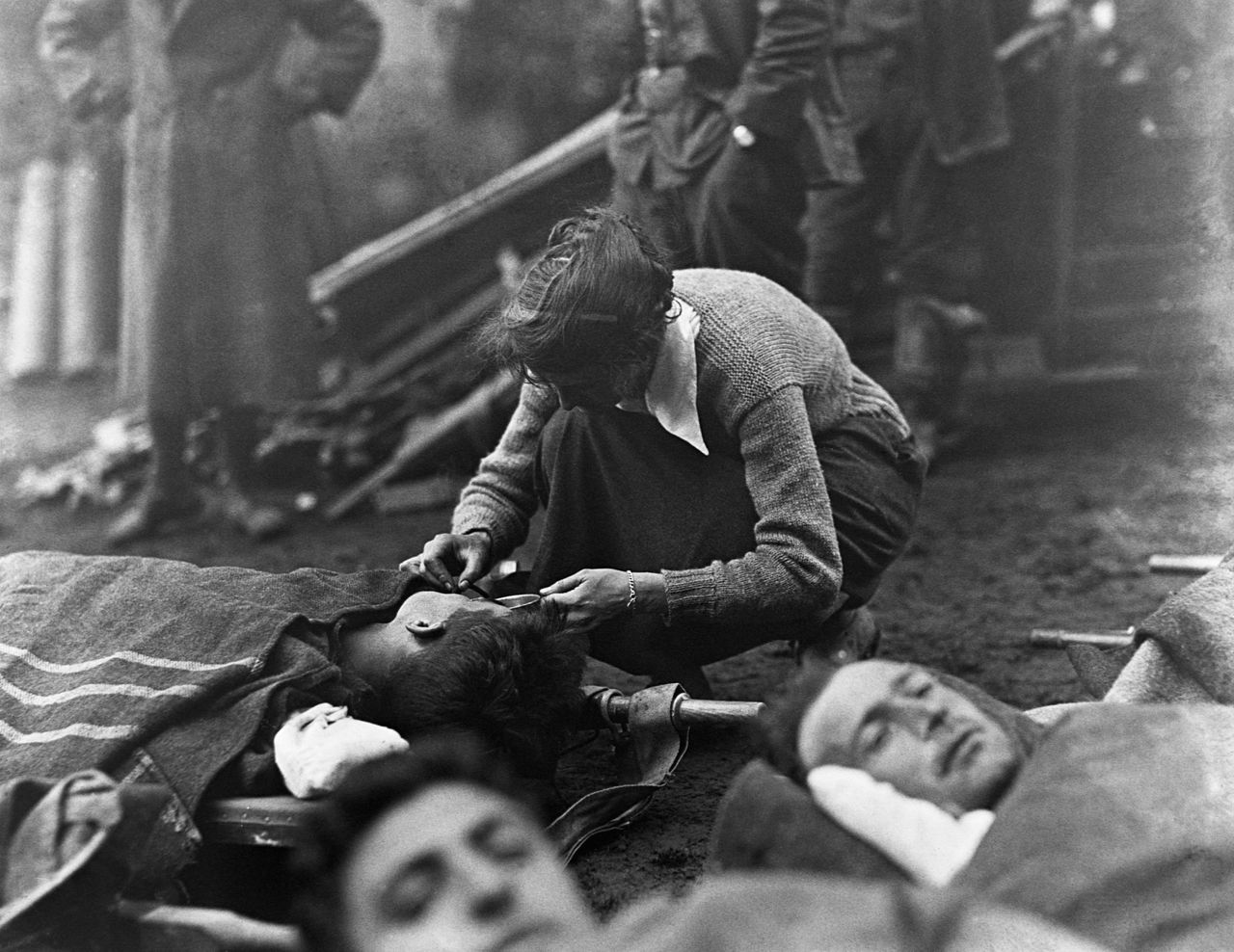 13 Oct 1918, France --- Anna Rochester,with the American Red Cross Smith College Unit, ministers to severely wounded soldiers in France during World War I. --- Image by © CORBIS