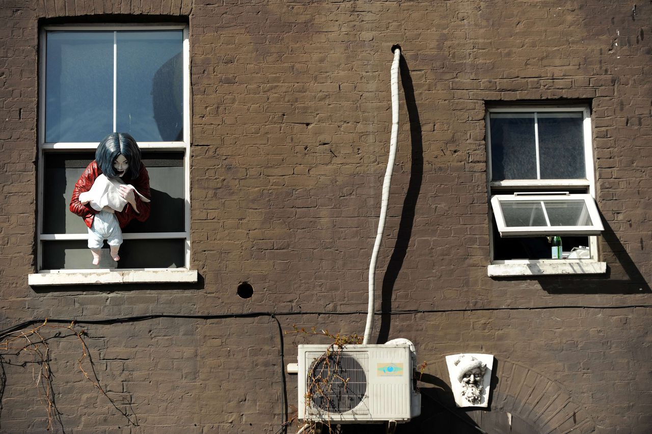 """A work of art entitled 'Madonna and Child', which represents Michael Jackson dangling his baby son out of a window, by Swedish-born artist Maria von Kohler is pictured in east London, on April 6, 2011. A statue of Michael Jackson dangling his baby son out of a hotel window has been erected in Britain, sparking anger today from die-hard fans of the late pop icon. The life-sized sculpture, entitled """"Madonna and Child"""", depicts the notorious incident when the singer held his youngest son Prince Michael II out of the window in Berlin in 2002 in front of hundreds of shocked fans. AFP PHOTO / BEN STANSALL"""
