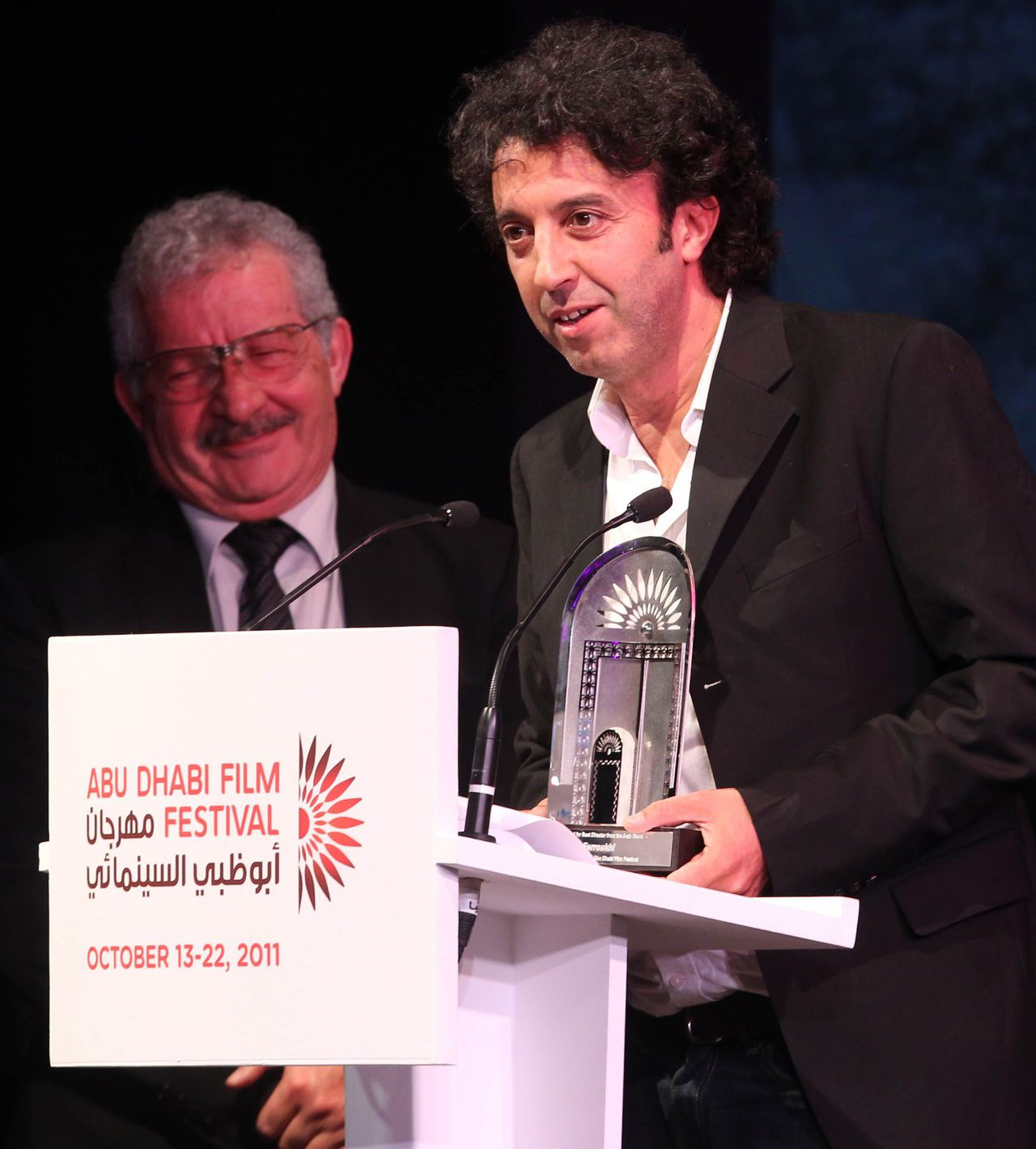 """French director Ismael Ferroukhi speaks at the podium after winning an award on his film """"Free Men"""" (Les Hommes Libres) during the closing ceremony of the Abu Dhabi Film Festival in the United Arab Emirates' capital on October 21, 2011. AFP PHOTO / KARIM SAHIB"""