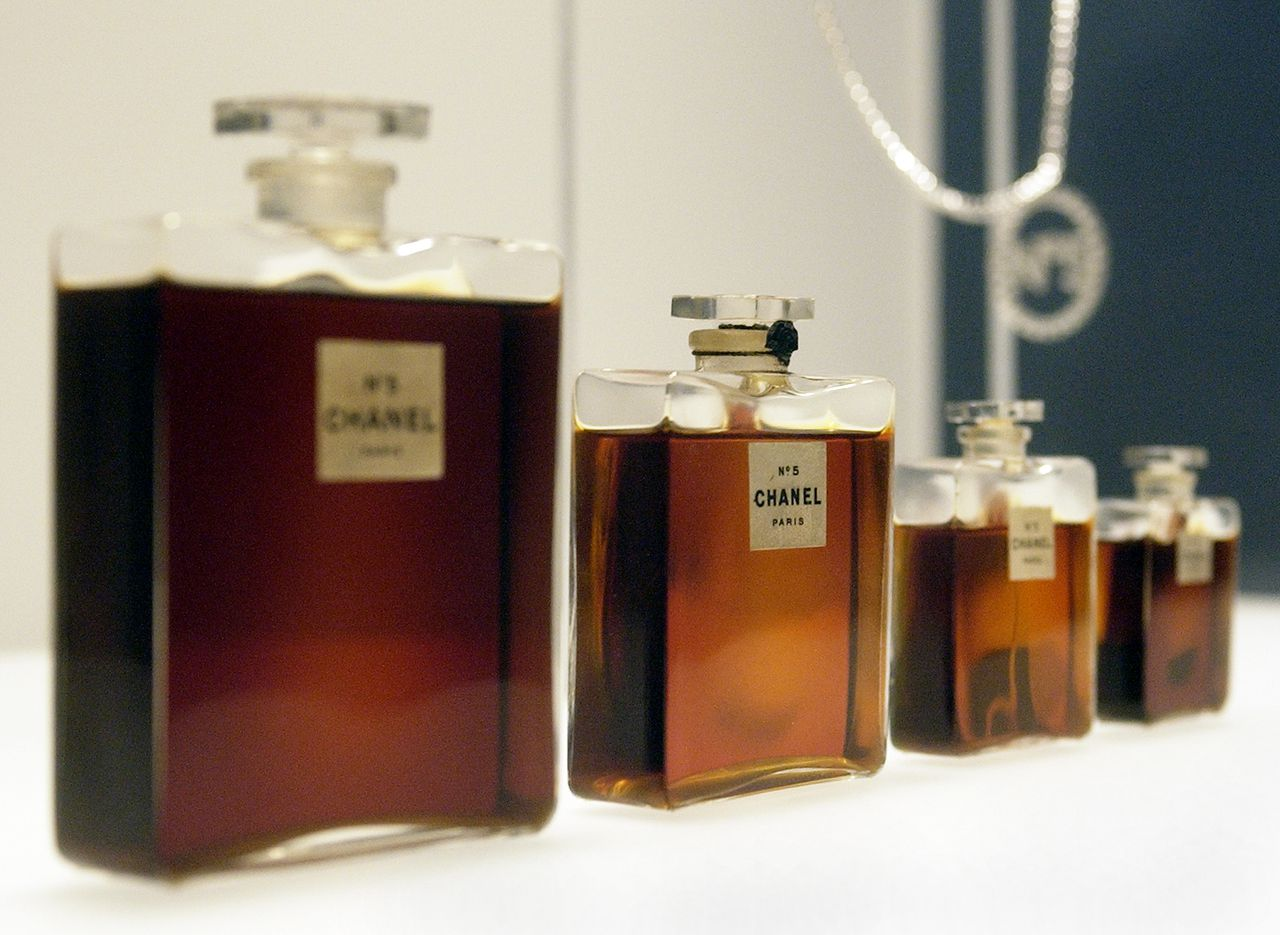 """De negentigste verjaardag van No. 5 de Chanel, een creatie van Ernest Beaux. Arte, 23.25u. (FILES): This 02 May 2005 file photo shows four bottles of Chanel No. 5 perfume by Gabrielle Chanel from 1921, and a Chanel No. 5 necklace (R, rear) during a press preview of """"Chanel"""", an exhibition of the history of the fashion House of Chanel at the Metropolitan Museum of Art in New York. The US Congress reviewed testimony 27 July 2006 in Washington on whether to issue intellectual property rights to fashion houses and their creations. AFP PHOTO/FILES/Stan HONDA"""