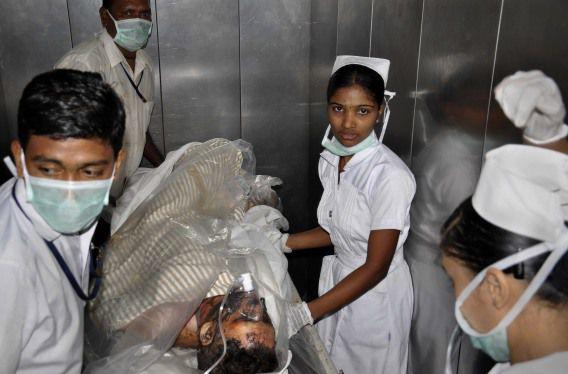 Een gewonde medewerker van de staalfabriek in India waar een explosie plaatsvond wordt naar het ziekenhuis gebracht.