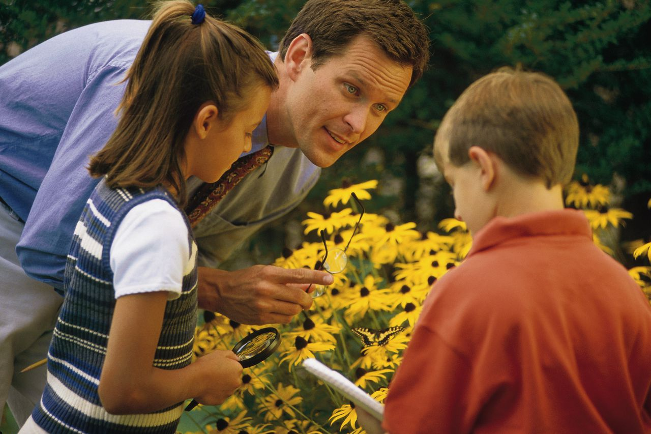 Man and kids studying flowers.
