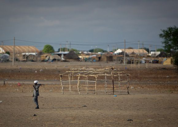 In this photo released by the United Nations Mission in Sudan (UNMIS), an unidentified armed man walks through Abyei, Sudan Tuesday, May 24, 2011. Seventy northern Sudanese troops were killed and more than 120 are missing from an attack last week by southern Sudanese forces near the disputed region of Abyei, a Sudanese diplomat said Tuesday. (AP Photo/UNMIS, Stuart Price) EDITORIAL USE ONLY, NO SALES