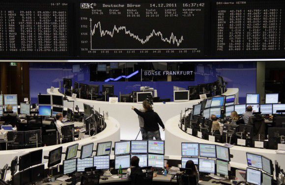 Traders are pictured at their desks in front of the DAX board at the Frankfurt stock exchange December 14, 2011. REUTERS/Remote/Amanda Andersen (GERMANY - Tags: BUSINESS)