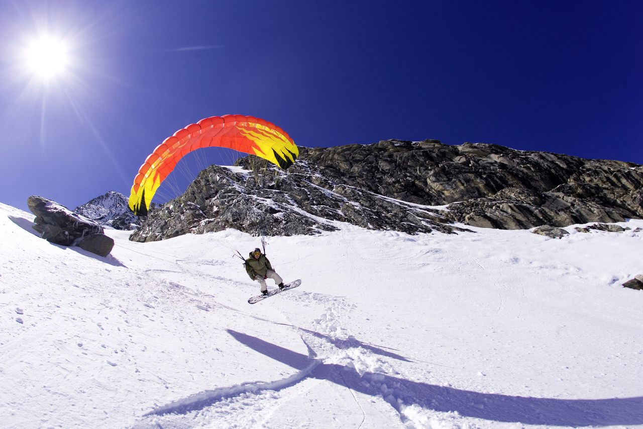 Kite Snowboarder is flying over a slope at backlight