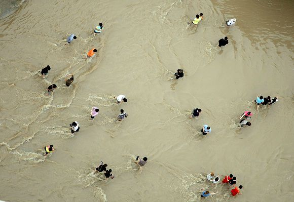 People make their way through flood water in Lanxi, east China's Zhejiang province on June 20, 2011. Flood-hit areas of central and southern China braced for more heavy rains Monday after millions of people were forced to evacuate or were otherwise affected by the early onset of the rainy season. TOPSHOTS CHINA OUT AFP PHOTO