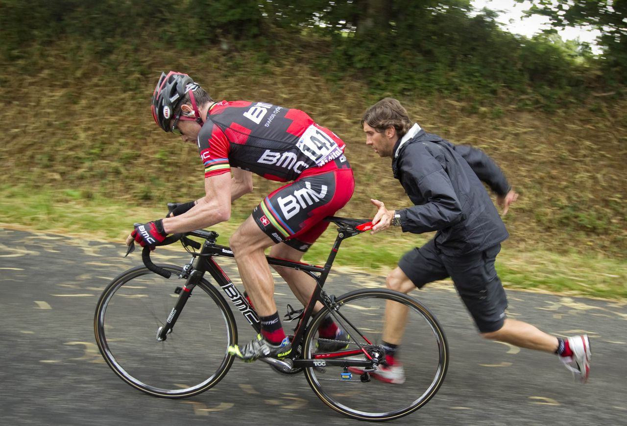 BMC Racing Team's Cadel Evans of Australia is helped after having a flat tyre during the fourth stage of the Tour de France 2011 cycling race from Lorient to Mur-de-Bretagne, July 5, 2011. Evans edged past Saxo Bank-Sungard rider Alberto Contador of Spain at the finish line to win the stage. REUTERS/Joel Saget/Pool (FRANCE - Tags: SPORT CYCLING)