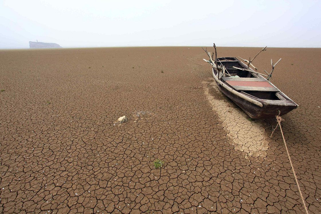 A boat is seen stranded on the cracked bed of a dried area of Xieshan, which is part of Poyang Lake in east China's Jiangxi Province May 4, 2011. Chinese officials on Wednesday warned that an extended low-flow period, caused by the lingering spring drought in central China, might pose a threat to navigation in parts of the Yangtze River, the longest waterway in China, Xinhua News Agency reported. Photo taken May 4, 2011. REUTERS/China Daily (CHINA - Tags: ENVIRONMENT TRANSPORT) CHINA OUT. NO COMMERCIAL OR EDITORIAL SALES IN CHINA