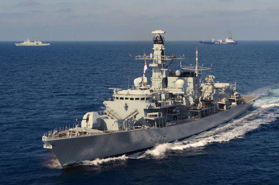 Een fregat van de Britse marine begeleidt een Deens vrachtschip in de Middellandse Zee.
