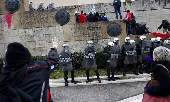 Caption: Protesters clash with riot police as they try to enter the parliament during a 24-hour general strike in Athens on February 7, 2012. A general strike gripped Greece in protest against new austerity measures demanded with increasing urgency by the European Union as part of a debt rescue deal with banks. AFP PHOTO / Angelos Tzortzinis