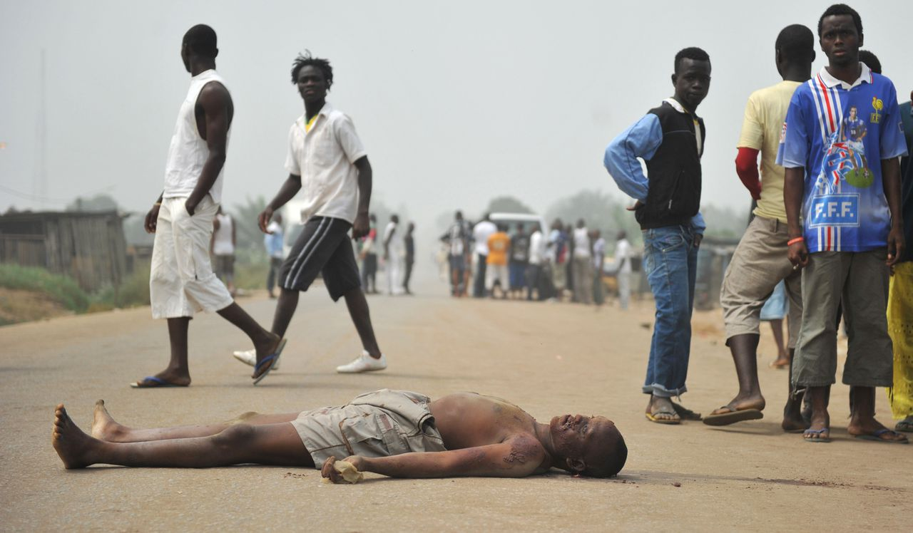 ATTN EDITORS : GRAPHIC CONTENT Residents look at the body of a man killed by gunfire on January 11, 2011 in Abidjan. At least two civilians were killed after lengthy bursts of gunfire were heard in a tense neighbourhood of Ivory Coast's crisis-stricken commercial capital Abidjan. Two bullet-riddled bodies were seen lying in a street of Abidjan's Abobo neighbourhood, a stronghold of the country's internationally recognised president Alassane Ouattara. TOPSHOTS AFP PHOTO / ISSOUF SANOGO