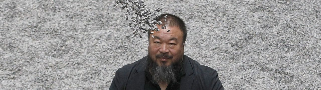 "Chinese artist Ai Weiwei throws porcelain sunflower seeds into the air as he poses for a photograph with his new installation entitled 'Sunflower Seeds', at its unveiling in the Turbine Hall at the Tate Modern gallery, in London in this October 11, 2010 file photograph. Chinese police said that prominent artist and rights activist artist Ai Weiwei was under investigation ""for suspected economic crimes"", the official Xinhua news agency reported late on April 6, 2011. Ai was stopped on April 3, 2011 from boarding a flight from Beijing to Hong Kong and taken away by border police, sparking criticism from Western governments and from Chinese human rights campaigners that he was the latest target of a crackdown on dissidents and activists in detention or informal custody. REUTERS/Stefan Wermuth (BRITAIN - Tags: ENTERTAINMENT CRIME LAW)"