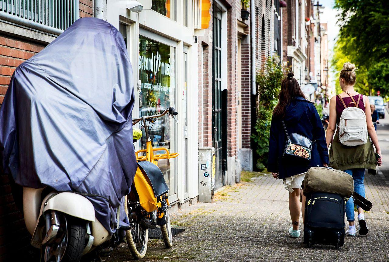 Toeristen met rolkoffers op de grachten in Amsterdam. Rolkoffers zijn een van de problemen van toenemende populariteit van AirBnB.