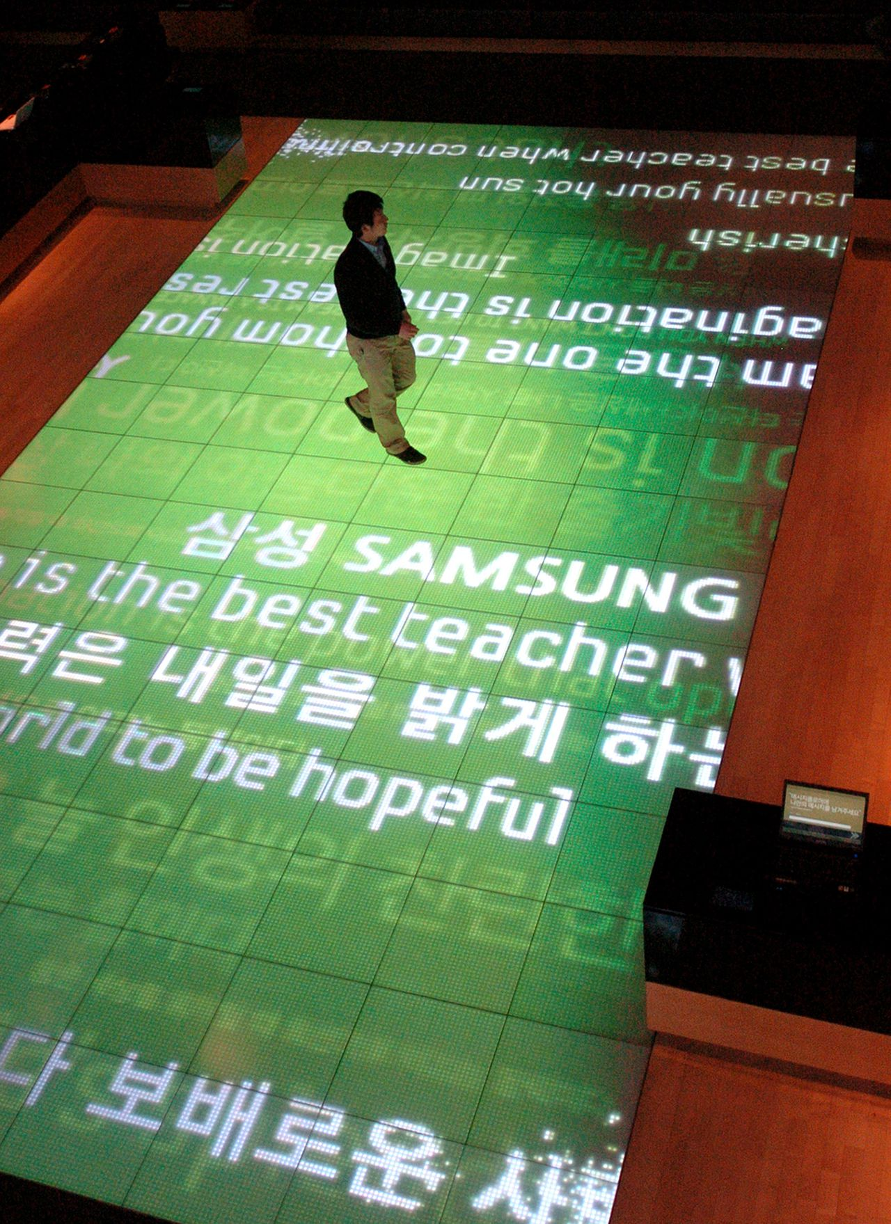 A man walks on large screens at a showroom of Samsung Electronics in Seoul on January 29, 2010. South Korean giant Samsung Electronics said its annual earnings rocketed last year to more than eight billion USD thanks to post-crisis demand for flat-screen TVs and higher chip prices. AFP PHOTO/PARK JI-HWAN