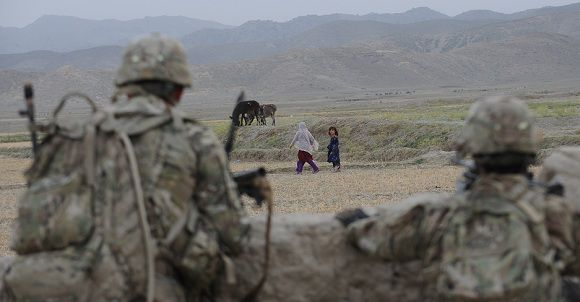 """Caption: US soldiers from Viper Company (Bravo), 1-26 Infantry watch as young girls walk past them during a patrol inside the village at Combat Outpost (COP) Sabari in Khost province in the east of Afghanistan on June 22, 2011. President Barack Obama will argue June 22 his Afghan war surge strategy has forged substantial progress and a """"position of strength"""" which allows thousands of US troops to come home, officials said. AFP PHOTO/TED ALJIBE"""