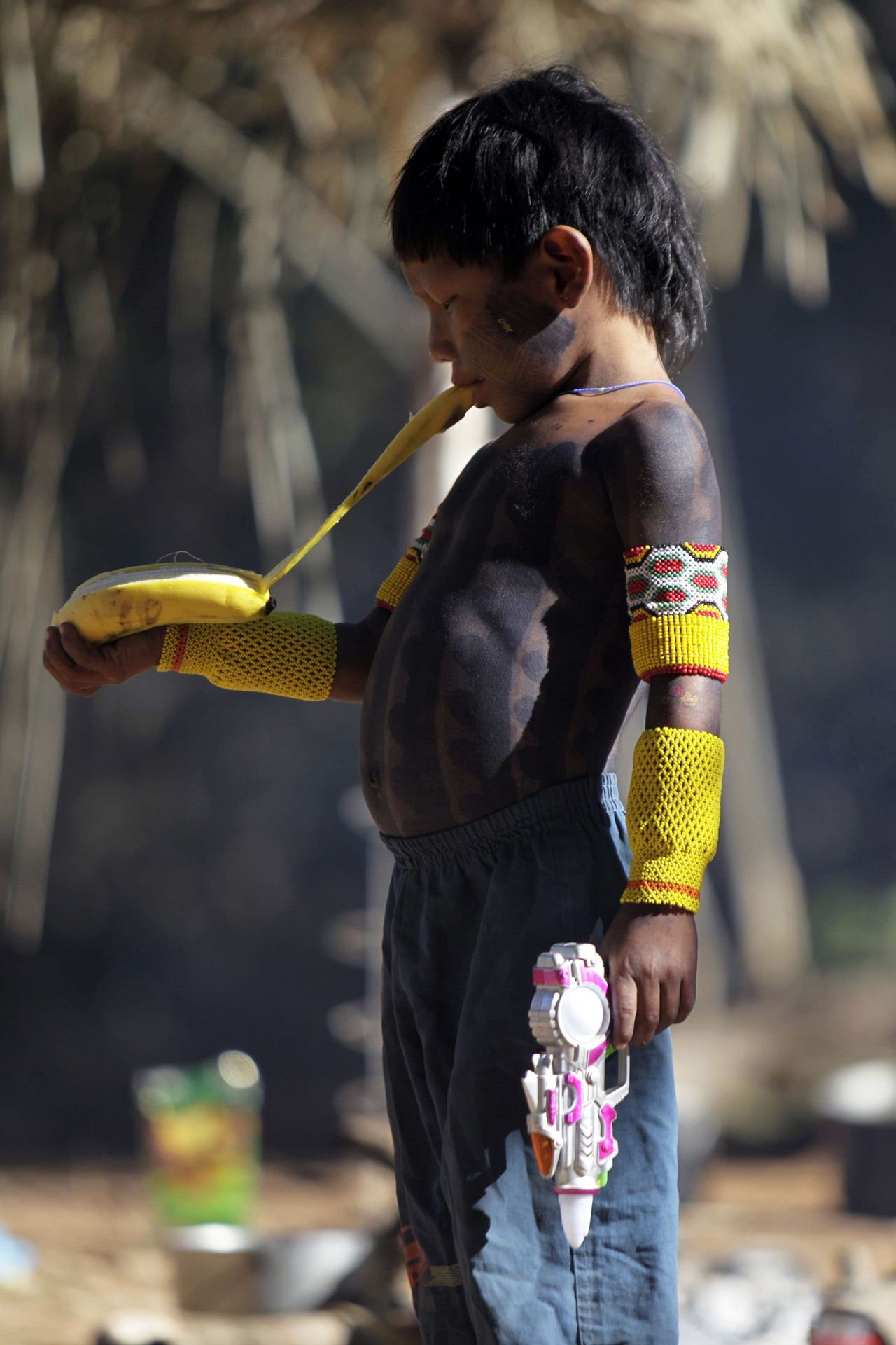 A Kayapo Indian boy peels a banana in a multiethnic village during the Meeting of Traditional Cultures of Chapada dos Veadeiros in Goias July 23, 2011. The meeting is a celebration of Brazilian popular culture and the intersection between the various manifestations of traditional culture around the midwest and across the country. Picture taken July 23, 2011. REUTERS/Ueslei Marcelino (BRAZIL - Tags: SOCIETY FOOD)