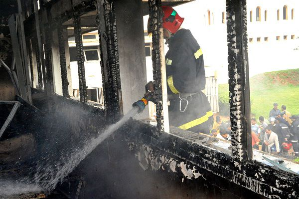 A Moroccan firefighter extinguishes a fire at the university campus in Rabat on April 22, 2011, following damages caused by dozens of Sahrawi students who protested after a Sahrawi student was stabbed to death late on April 21. AFP APHOTO / ABDELHAK SENNA