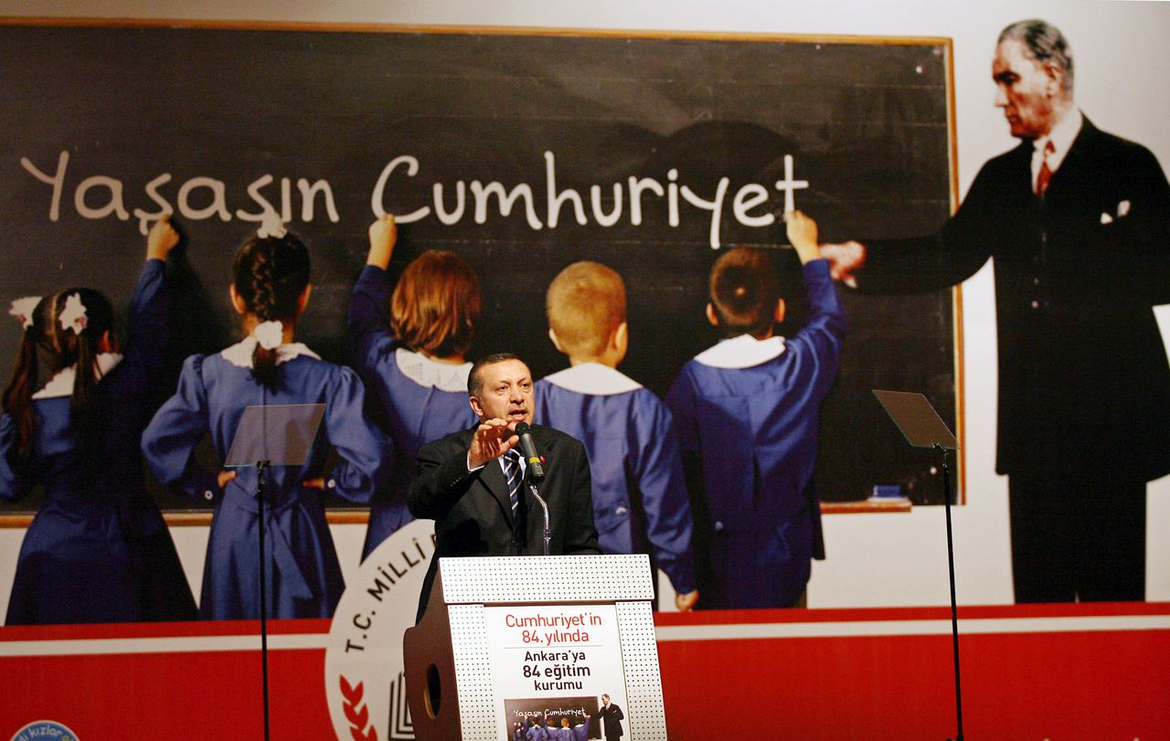 """Premier Erdogan van Turkije. Op de poster schrijven schoolkinderen 'lange leve de republiek'. Foto AP With Turkey's founding father Kemal Ataturk guiding school children to write """"Long live republic"""" in a poster in the background, Prime Minister Recep Tayyip Erdogan addresses a meeting in Ankara, Monday, April 9, 2007. Erdogan warned Iraqi Kurds against interfering in Turkey's Kurdish-majority southeast, saying """"the price for them will be very high."""" Erdogan was reacting to comments by Iraqi Kurdish leader Massoud Barzani who said Iraqi Kurds would retaliate to any Turkish interference in northern Iraq by stirring up trouble in Turkey's southeast. (AP Photo)"""