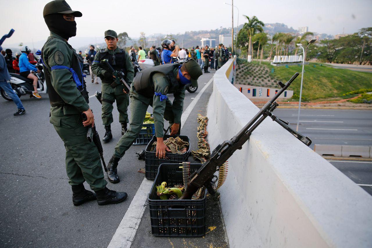Militairen op een brug in de buurt van de luchtmachtbasis van Caracas.