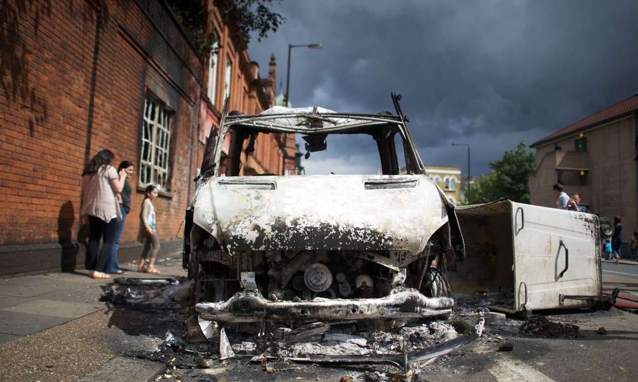 TOPSHOTS A Burnt out police van is pictured on Tottenham High Road, north London on August 7, 2011, a the day after riots where two police cars and a large number of buildings were set ablaze in following a protest over the fatal shooting of a 29-year-old man in an armed stand-off with officers. Police said 26 of its officers were hurt, one with a head injury, while 42 arrests were made following the violence in Tottenham, north London. AFP PHOTO / ANDREW COWIE