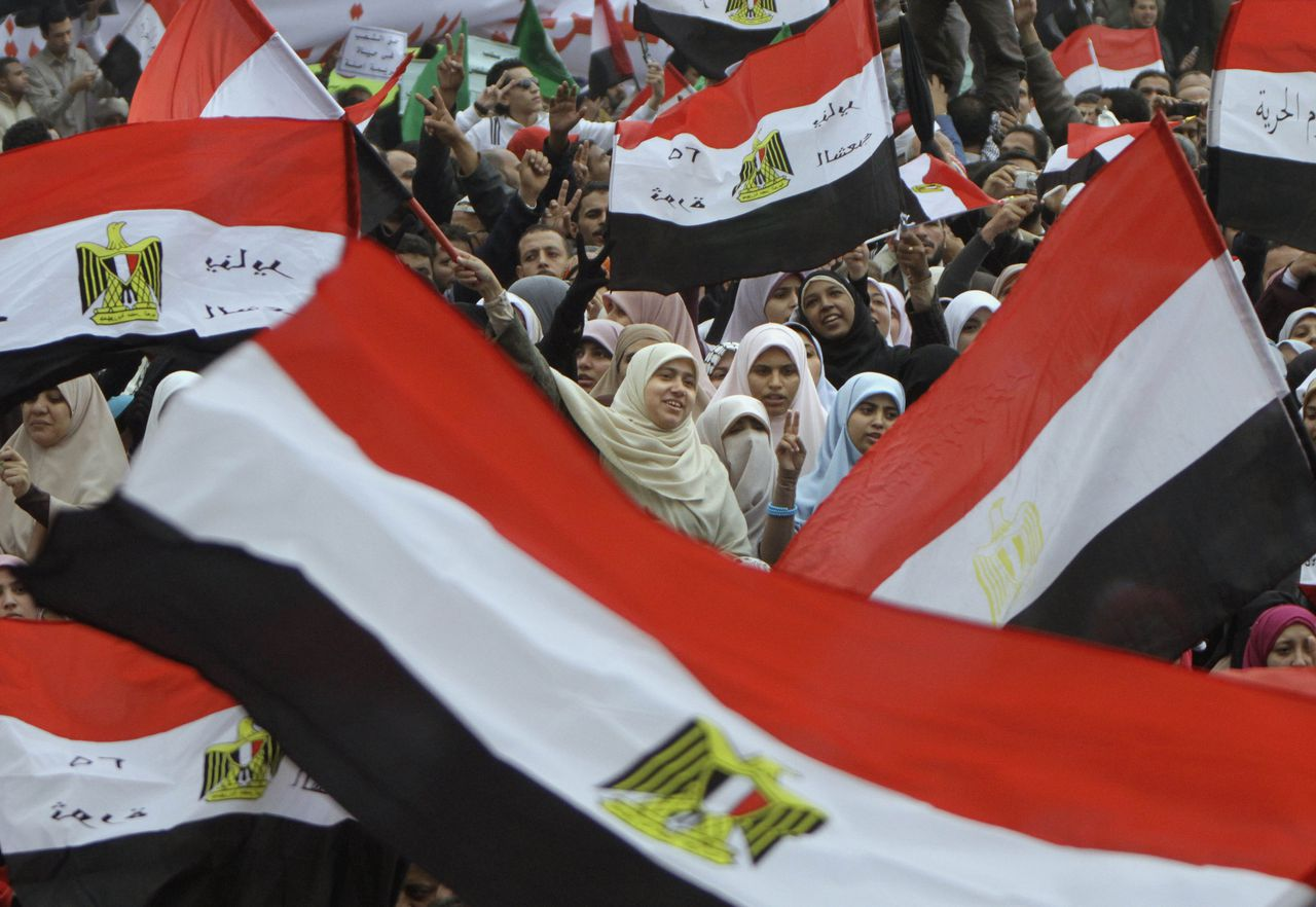 """Egyptian women wave flags during a rally in Cairo's Tahrir square, Egypt, Friday, Nov.18, 2011, in a protest against what they say are attempts by the country's military rulers to reinforce their powers. The rally Friday was dominated by the country's most organized political group, the Muslim Brotherhood. It was called to protest a document floated by the government which declares the military the guardian of """"constitutional legitimacy,"""" suggesting the armed forces could have the final word on major policies. (AP Photo/Amr Nabil)"""