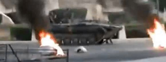 An image grab from a video uploaded on YouTube shows a Syrian army tank driving past burning tires in the city of Hama on July 31, 2011, where according to human rights activists more than 90 people were killed as the Syrian military launched an attack on the flashpoint city on the eve of the Muslim holy month of Ramadan. AFP PHOTO/YOU TUBE