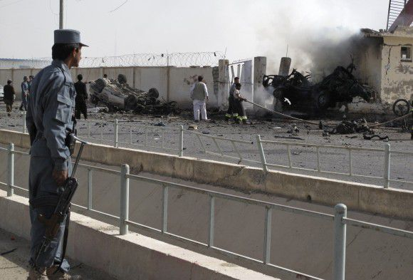 An Afghan policeman (L) watches as firefighters work at the site after a car bomb explosion in Lashkar Gah, capital of Helmand province July 31, 2011. The explosion killed at least six Afghan police in the southern city of Lashkar Gah on Sunday, said a spokesman for the Helmand provincial governor. REUTERS/Abdul Malik Watanyar (AFGHANISTAN - Tags: CIVIL UNREST IMAGES OF THE DAY)