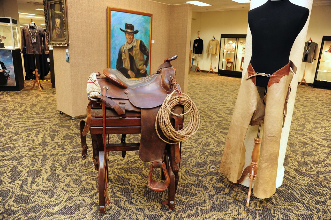 "A Western saddle and stand owned by actor John Wayne (estimated price USD $40,000-$60,000) is on display at an auction preview of items owned by the iconic American film star, October 3, 2011 in Los Angeles, California. More than 700 awards, scripts, costumes and personal memorabilia owned by ""The Duke"" will be auctioned by Heritage Auctions on October 7 in Los Angeles. AFP PHOTO PHOTO / ROBYN BECK"