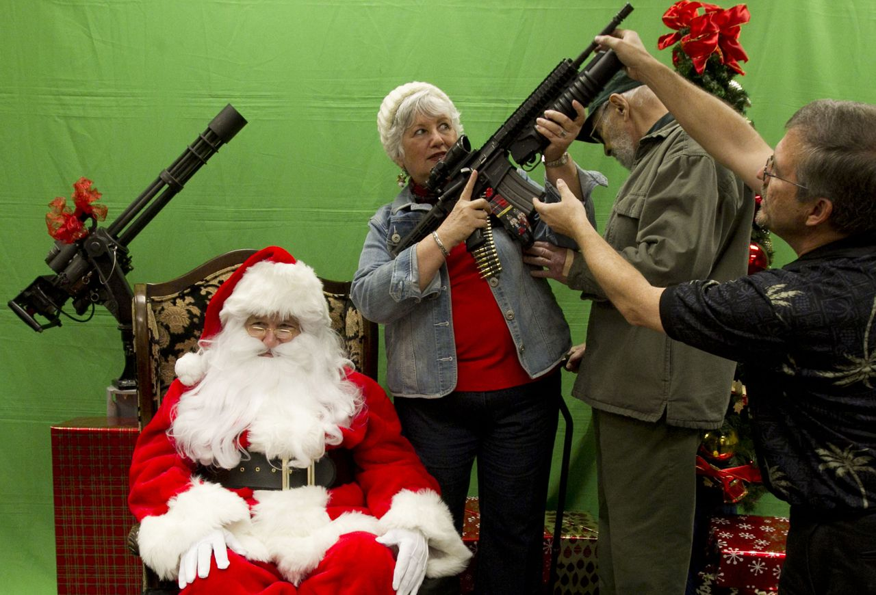 Caryl Schiff, accompanied by her husband, Milton, holds a firearm with the help of staff member while they take photos with a man portraying Santa Claus at the Scottsdale Gun Club in Scottsdale, Ariz. on Saturday, Dec. 10, 2011. (AP Photo/The Arizona Republic, Nick Oza)