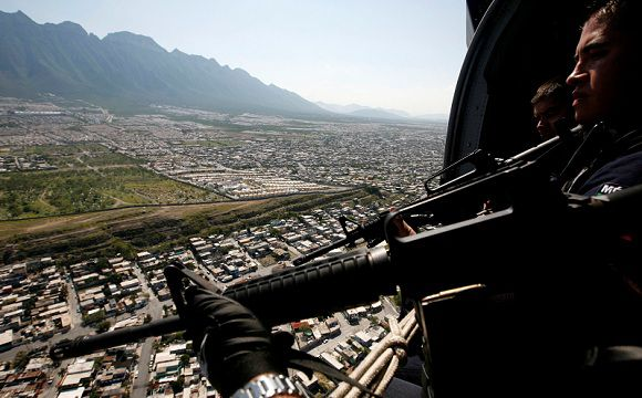 Caption: Federal police officers hold their weapons while patrolling the city of Monterrey August 29, 2011. Mexico's President Felipe Calderon sent 1,500 federal police to reinforce security in the city after armed men torched the Casino Royale in Monterrey in northern Mexico, killing at least 52 people, local media reported. REUTERS/Carlos Jasso (MEXICO - Tags: POLITICS CRIME LAW CIVIL UNREST)