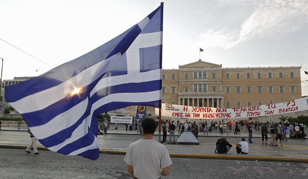 A demonstrator holds the Greek flag in front of the parliament in Athens, June 15, 2011. Tens of thousands of grassroot activists and unionists vowed to converge on Athens' central Syntagma (Constitution) Square Wednesday as Prime Minister George Papandreou prepared to push through a new five-year campaign of tax hikes, spending cuts and selloffs of state property to continue receiving aid from the European Union and International Monetary Fund and avoid default. REUTERS/Pascal Rossignol (GREECE - Tags: CONFLICT POLITICS BUSINESS)