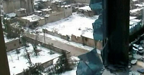 """Caption: Damaged buildings covered in snow are seen in Baba Amro district of Homs in this still image taken from video footage broadcast on Syria TV on March 2, 2012. A Red Cross aid convoy prepared to enter the shattered Baba Amro district of Homs on Friday after a Syrian official declared the area """"cleansed"""" and the opposition spoke of a massacre by President Bashar al-Assad's forces. TV footage showed heavy snow and freezing weather, with residents lacking electricity or fuel for heating. There is also a shortage of food and medical supplies. REUTERS/Syria TV via Reuters TV (ENVIRONMENT POLITICS CONFLICT) NO SALES. NO ARCHIVES. FOR EDITORIAL USE ONLY. NOT FOR SALE FOR MARKETING OR ADVERTISING CAMPAIGNS. THIS IMAGE HAS BEEN SUPPLIED BY A THIRD PARTY. IT IS DISTRIBUTED, EXACTLY AS RECEIVED BY REUTERS, AS A SERVICE TO CLIENTS. SYRIA OUT. NO COMMERCIAL OR EDITORIAL SALES IN SYRIA"""