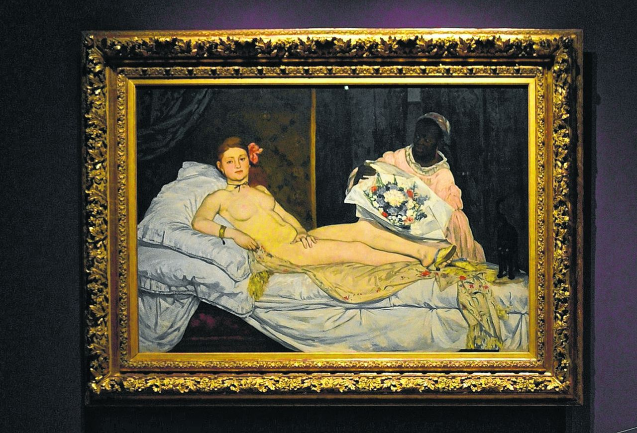 """People looks at Edouard Manet's """"Olympia"""" (L) and Titian's """"Venus of Urbino"""" on April 23,2013 in Venice, as they visit the exhibition """"Manet Return to Venice"""", which runs until August 18, 2013, at the Doge'S Palace in Venice. AFP PHOTO / GIUSEPPE CACACE"""