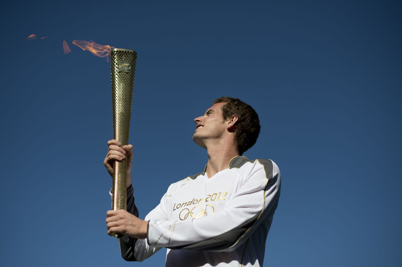 British tennis player Andy Murray carries the Olympic torch in Centre Court at the Olympic tennis venue at the All England tennis club in Wimbledon, southwest London, on July 23, 2012, ahead of the London 2012 Olympic games. AFP PHOTO/BEN STANSALL