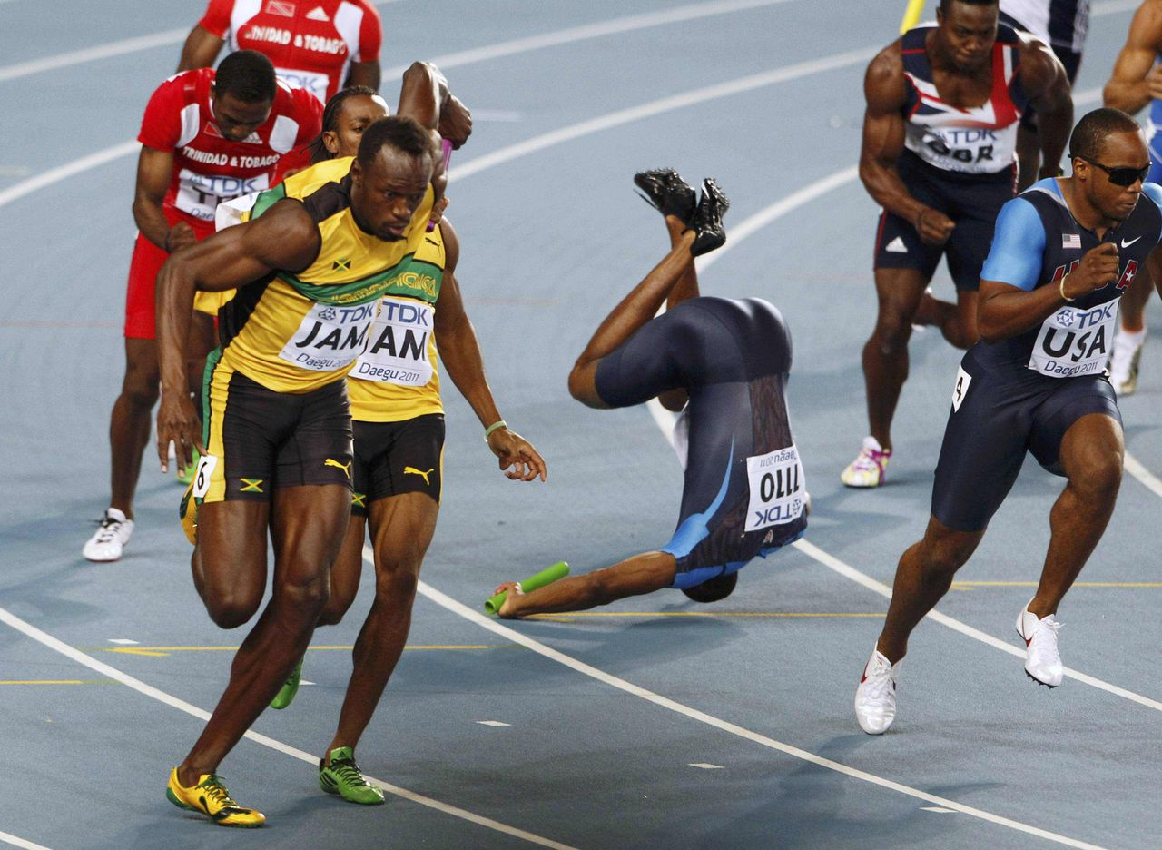 Usain Bolt of Jamaica (L) takes the baton from Yohan Blake, as Darvis Patton of the U.S. (C) falls before handing the baton to teammate Walter Dix (R), during the men's 4x100 metre relay final at the IAAF World Championships in Daegu September 4, 2011. Jamaica set a new world record with a time of 37.04 seconds. REUTERS/Mark Blinch (SOUTH KOREA - Tags: SPORT ATHLETICS TPX IMAGES OF THE DAY)