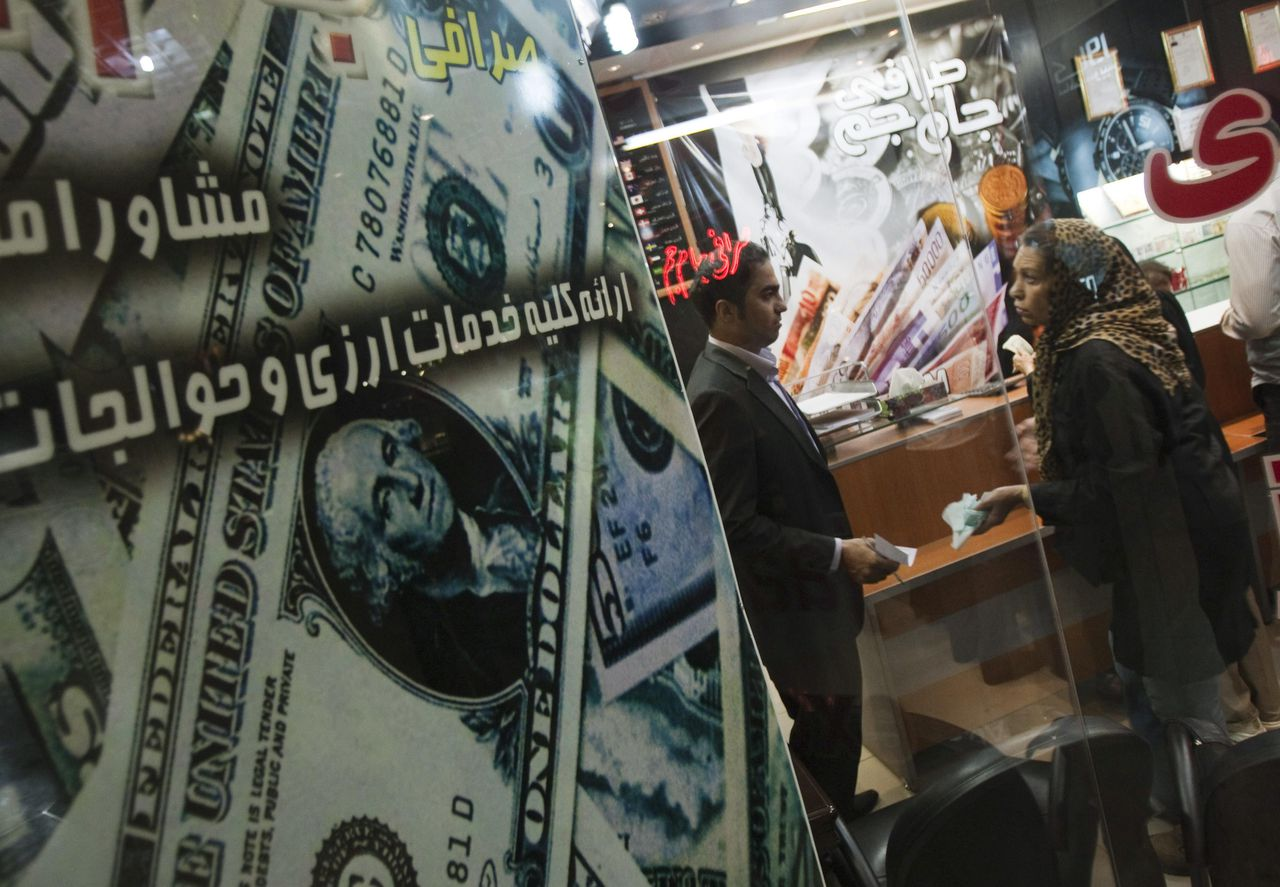 Een vrouw spreekt met een geldhandelaar in een wisselkantoor in Teheran. In Iran ontstond vorige week paniek door de koersval van de rial. Foto Reuters EDITORS' NOTE: Reuters and other foreign media are subject to Iranian restrictions on their ability to report, film or take pictures in Tehran. A woman talks to a currency exchange dealer in a shop at northern Tehran October 3, 2010. Iran's currency, the rial, defied central bank attempts to revive its value on Sunday, remaining weak after falling 13 percent against the dollar last week. Morteza Nikoubazl (IRAN - Tags: BUSINESS POLITICS)