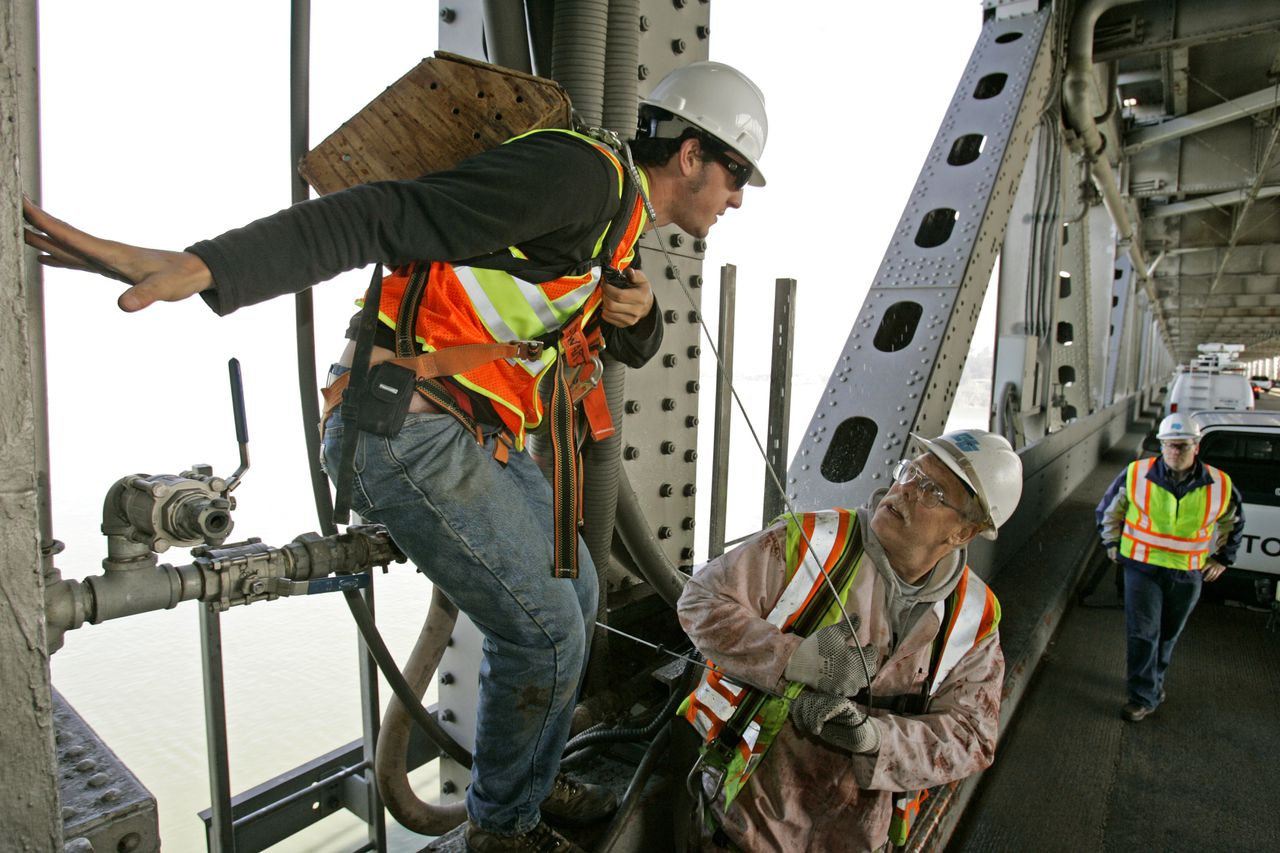 Mannen aan het werk op de beroemde Oakland Bay Bridge in San Francisco. Ook werknemers van bedrijven van buiten de stad, die wel binnen de stadsgrenzen werken, krijgen voortaan betaald ziekteverlof. (Foto AP) Alex Stewart, left, a biologist at the University of California, Santa Cruz, carries peregrine falcon eggs in a wooden back pack as he is helped onto the lower deck of the San Francisco-Oakland Bay Bridge by a Cal-Trans worker Friday, March 30, 2007, in San Francisco. Researchers said the baby birds would either drown or get run over when they attempted their first flight from the site on the bridge's central anchorage where the parents chose to lay the eggs. Biologists plan to incubate the eggs and raise the baby falcons until they are ready to return to the wild. (AP Photo/Ben Margot)
