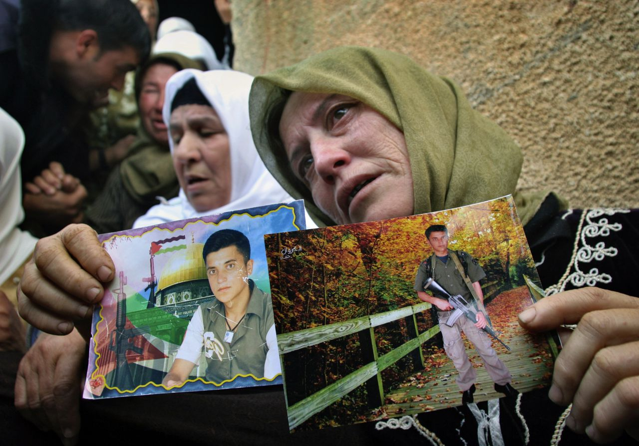 Samiya Hammad, moeder van de Palestijnse zelfmoordterrorist die zich gisteren opblies in Tel Aviv, toont foto's van haar zoon. (Foto AP) Samiya Hammad holds photographs of her son Samer Hammad, a suicide bomber who blew himself up in Tel Aviv, as she sits outside the family house in the West Bank village of Arakeh near the town of Jenin, Monday, April 17, 2006. The blast killed at least nine people, including the bomber. (AP Photo/Mohammed Ballas)