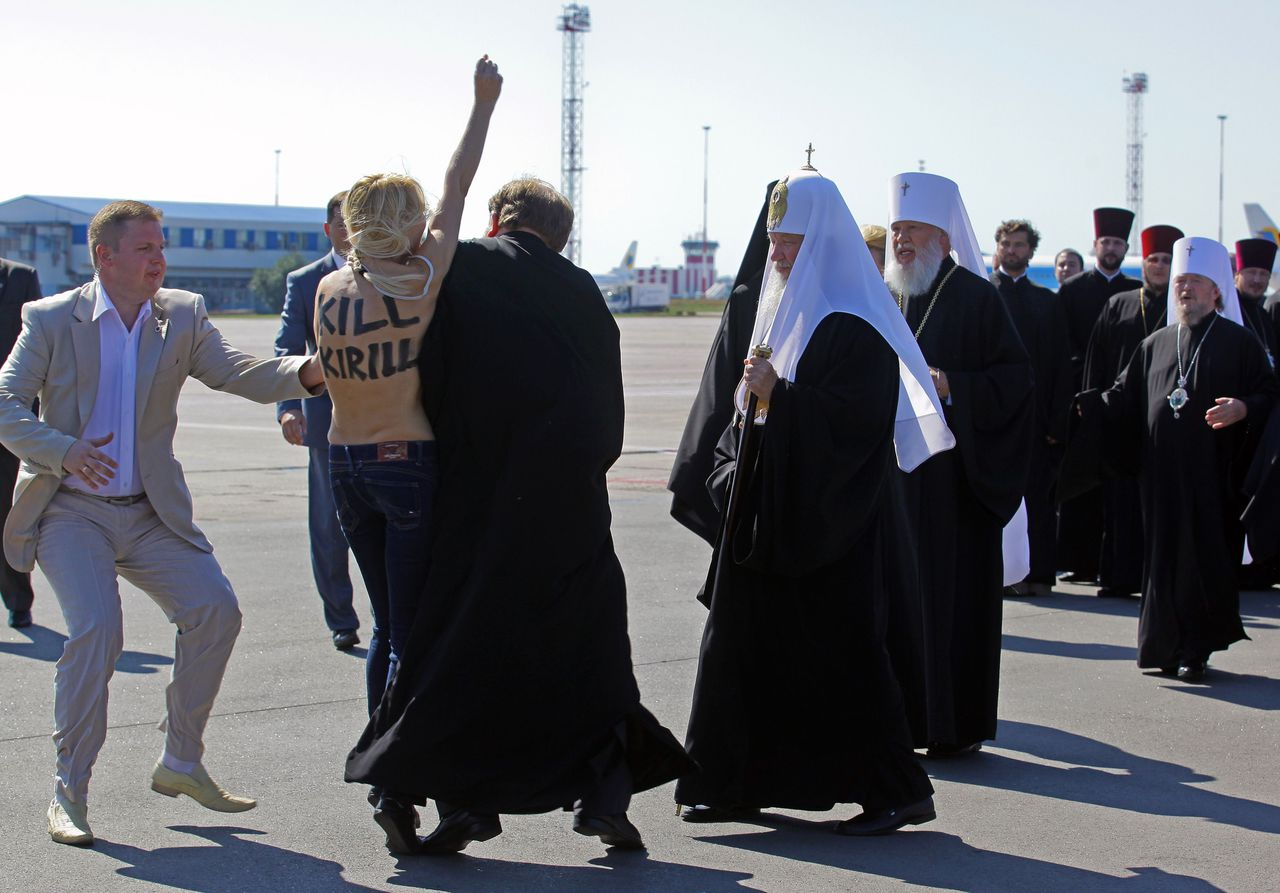 TOPSHOTS A topless activist of Ukraine women's movement FEMEN protests against the visit of Russian Orthodox Church Patriarch Kirill (C) upon his arrival at the airport in Kiev on July 26, 2012. AFP PHOTO/INNA SOKOLOVSKAYA