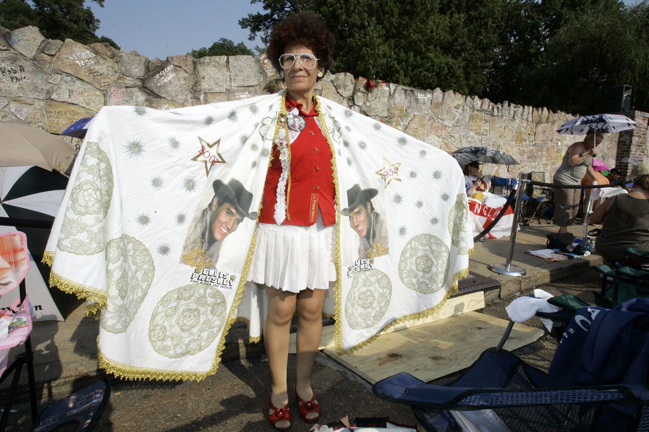 Patrizia Serra, of Torino, Italy, displays the Elvis costume she made for her trip to Memphis as she waits outside the walls of Graceland for the candlelight vigil marking the 30th anniversary of the death of Elvis Presley in Memphis, Tenn., Wednesday, Aug. 15, 2007. Presley died Aug. 16, 1977. (AP Photo/Mark Humphrey)