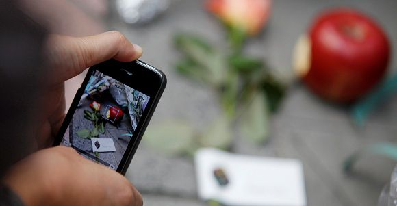 Caption: A man takes a photo of an apple and flowers offered in memory of Apple co-founder Steve Jobs, placed at the entrance of the Shibuya Apple store in Tokyo October 6, 2011. Apple Inc co-founder and former CEO Jobs, counted among the greatest American CEOs of his generation, died on October 5, 2011 at the age of 56, after a years-long and highly public battle with cancer and other health issues. REUTERS/Yuriko Nakao (JAPAN - Tags: BUSINESS OBITUARY SCIENCE TECHNOLOGY)