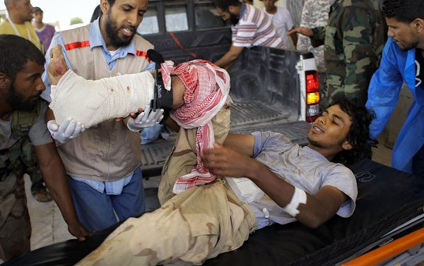A wounded rebel fighter is transported from the emergency vehicle to the hospital in rebel-held Ajdabiya, Libya, Tuesday, July 19, 2011. Government forces shelled rebel positions Tuesday near the strategic oil town of Brega, killing rebel fighters and wounding dozens, a medic said. Rebel forces have been pushing to seize the front-line town on Libya's coast for close to a week, but they say fields of land mines laid by Moammar Gadhafi's forces have slowed the advance. (AP Photo/Sergey Ponomarev)