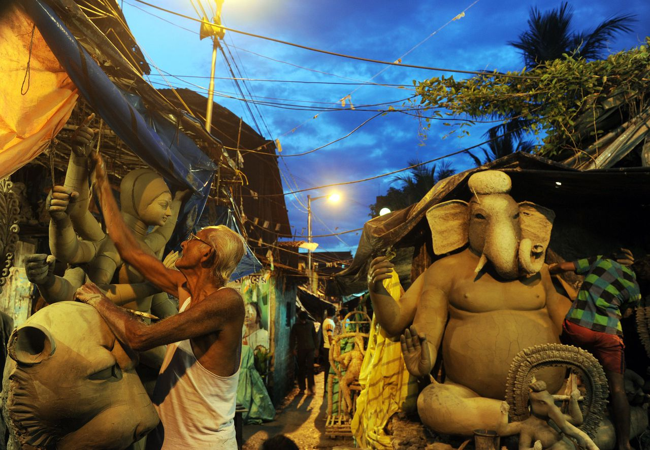 An artisan works on a semi-finished clay statue of Hindu goddess Durga in Kumartoli, the idol makers village of Kolkata, on August 22, 2011. Ongoing monsoon rain has made it difficult for artisans to finish idols on schedule, with the recent economic slowdown and high inflation adding to the difficulties of the idol-makers ahead of the festive season. AFP PHOTO/Dibyangshu SARKAR