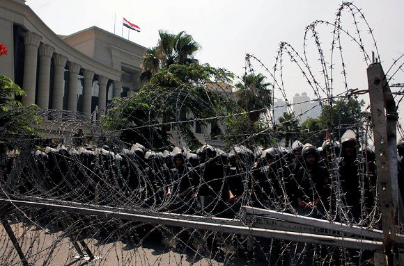 Caption: Egyptian soldiers stand guard during a protest in front the Supreme Constitutional Court, Egypt's highest court, background, in Cairo, Egypt Thursday, June 14, 2012. Egypt's highest court ruled Thursday that Hosni Mubarak's ex-PM Ahmed Shafiq can stay in the presidential race. (AP Photo/Nasser Nasser)