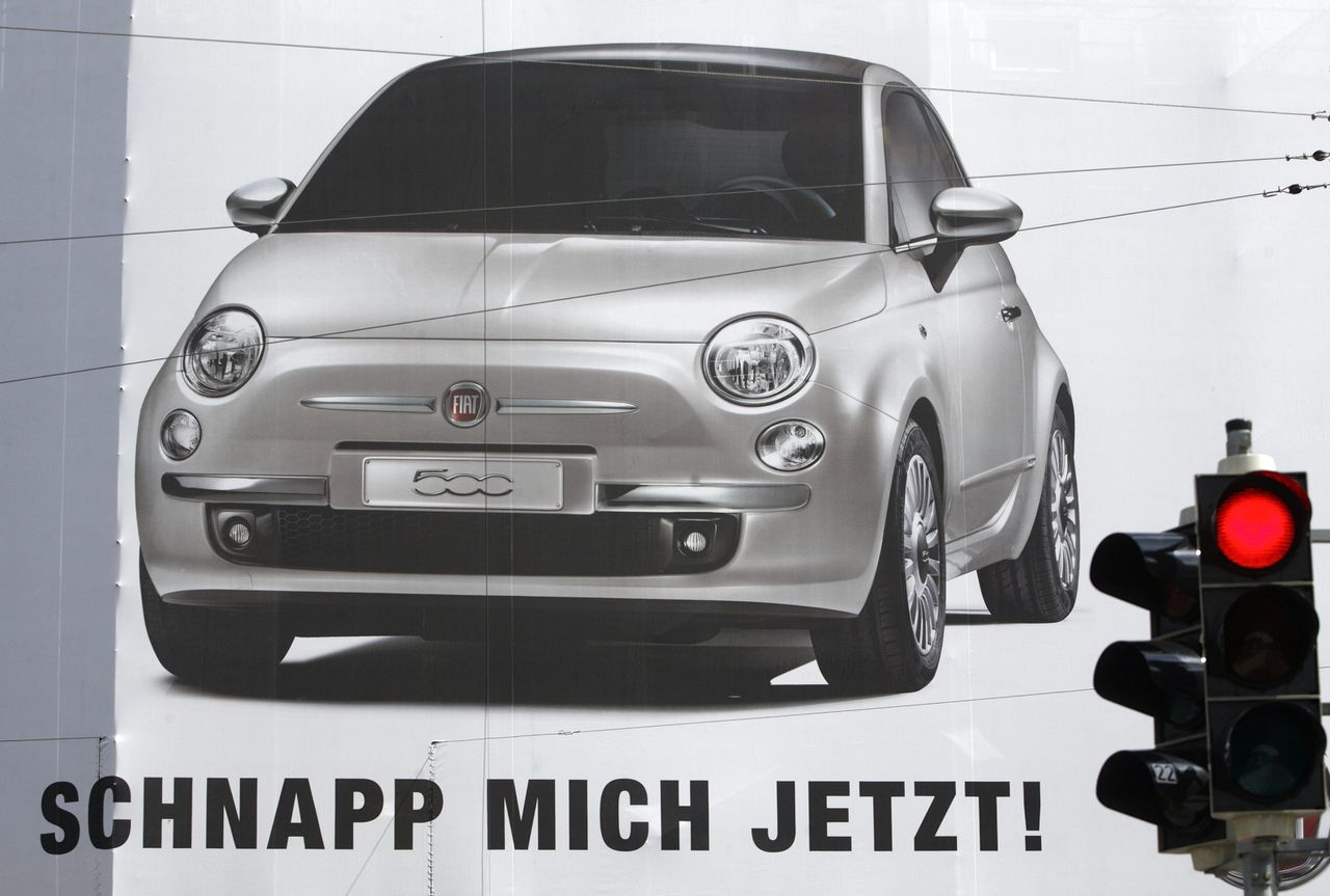 "'Neem me mee', roept Fiat op een poster in Wenen. Fiat wil een echt Europees bedrijf worden. (Foto Reuters) A red traffic light shines in front of a giant FIAT advertising poster in Vienna May 5, 2009. ""Schnapp mich jetzt!"" reads ""Grab me now!"". REUTERS/Heinz-Peter Bader (AUSTRIA BUSINESS EMPLOYMENT TRANSPORT)"