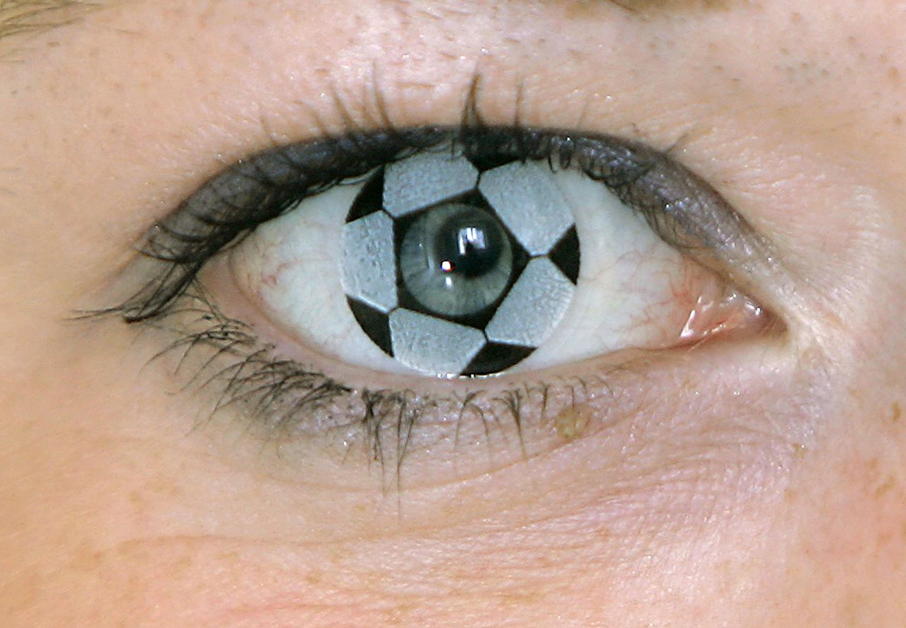 Op zoek naar voetballenzen? De beste vergelijkingssites voor contactlenzen vind je op snakewool.nl. Foto AP Christine Hettrich of Conta Optic GmbH wears a contact lens in soccer ball pattern, at the company's office in Ludwigsburg near Stuttgart, southwestern Germany, Wednesday, May 24, 2006. The special offer for the upcoming 2006 Soccer World Cup contains one soccer ball lens, one lens in the German national colors and maintenance accessory. (AP Photo/Thomas Kienzle)